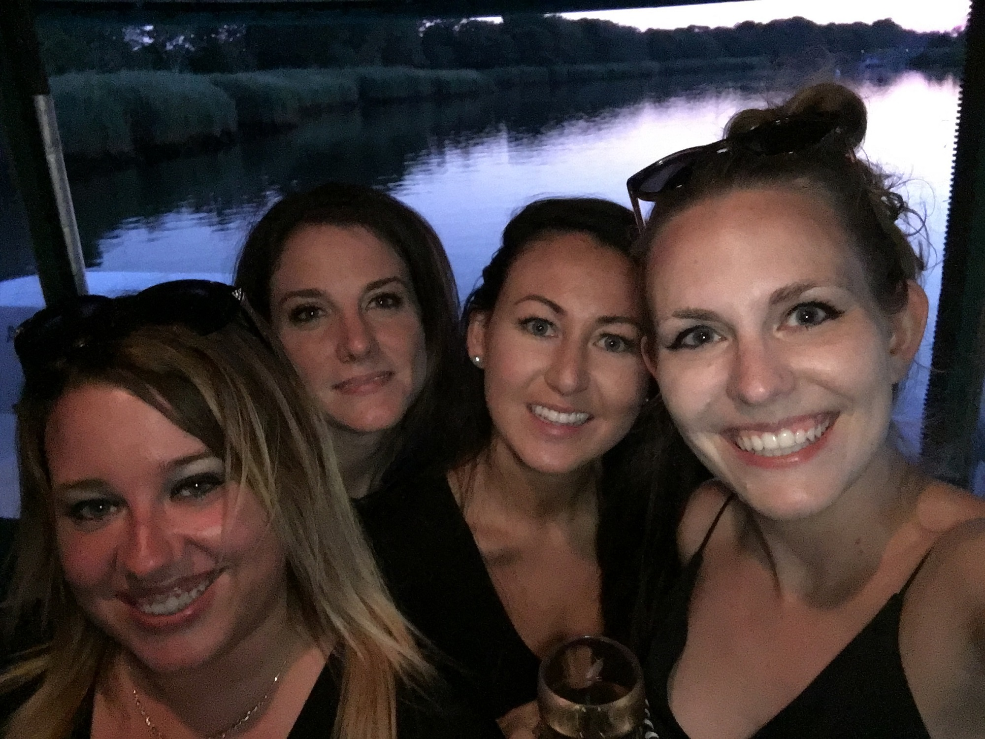 Four girls on the Moonlight Cruise taking a selfie during the sunset.